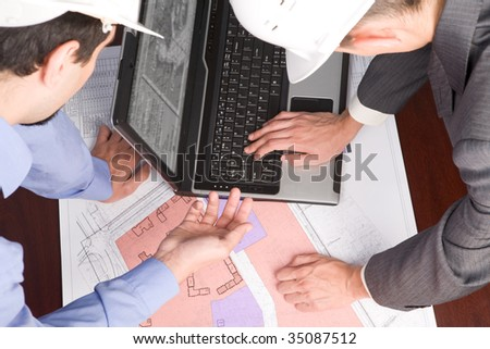 Above view of engineers looking at blueprints with sketches of projects while one of them typing on laptop keyboard - stock photo