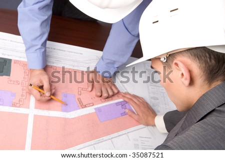 Above view of engineers over blueprints during discussion - stock photo