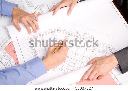 Above view of engineers over blueprints during work planning - stock photo