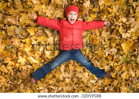 Above view of excited child shouting from happiness while lying on dry autumnal leaves - stock photo