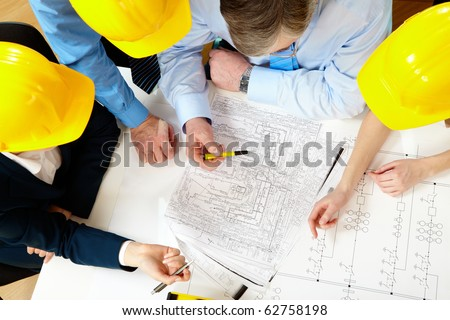 Above view of four architects sitting at the table and discussing design project - stock photo