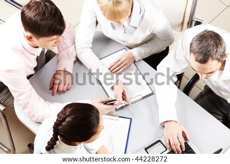 Above view of friendly workteam discussing business papers - stock photo
