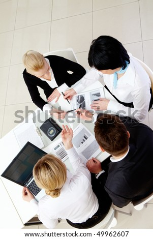Above view of friendly workteam interacting at meeting - stock photo