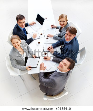 Above view of friendly workteam looking at camera during meeting - stock photo