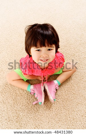 Above view of happy child sitting on the floor - stock photo