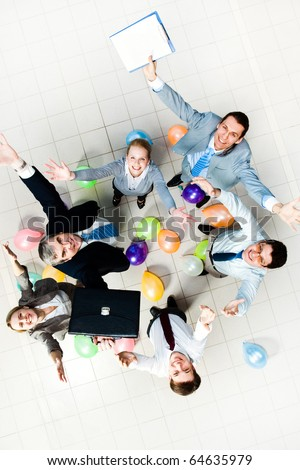 Above view of joyful business people looking at camera with balloons on the floor - stock photo