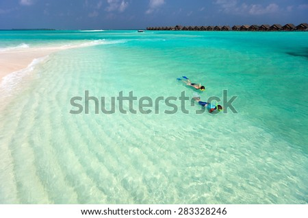 Above view of  mother and son snorkeling in a clear tropical water - stock photo