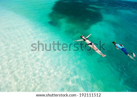 Above view of  mother and son swimming in a clear tropical ocean water during summer vacation - stock photo