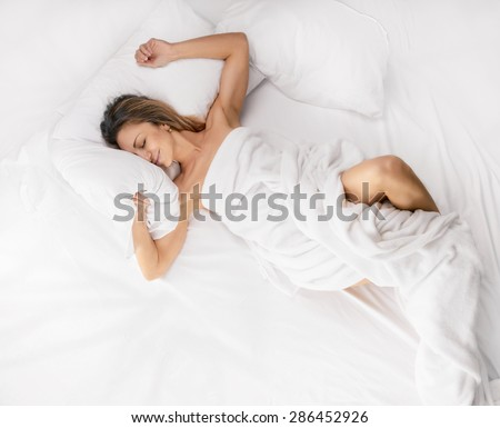 Above view of pretty female in peignoir lying on bed with smile. Above view - stock photo
