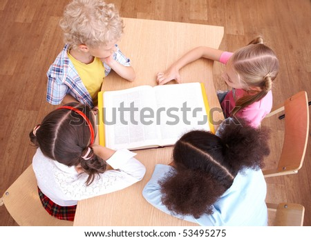 Above view of pupils looking at page of encyclopaedia at reading lesson - stock photo