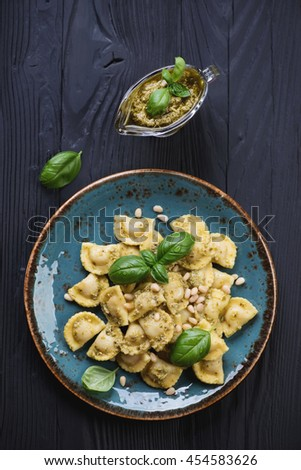 Above view of ravioli with basil pesto on a black wooden surface