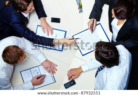 Above view of several business partners discussing contract - stock photo