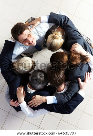 Above view of several business partners embracing each other while making circle with one of them looking at camera - stock photo