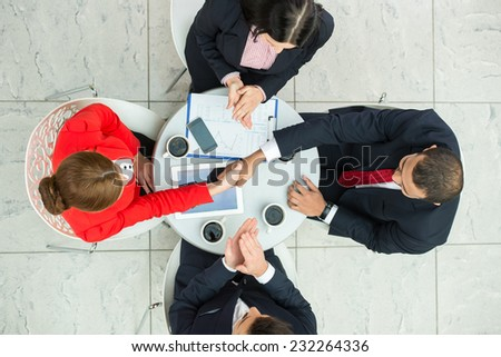 Above view of several business people are planning work at round table. - stock photo