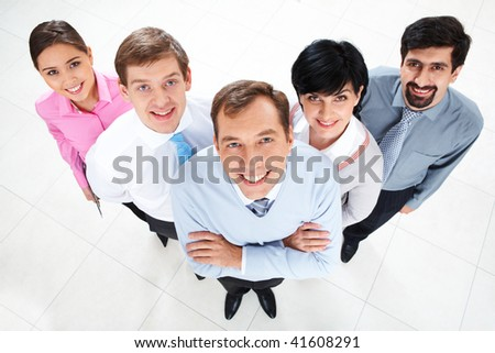 Above view of several successful partners looking at camera and smiling - stock photo