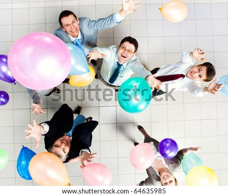 Above view of several successful partners throwing colorful balloons in joy - stock photo