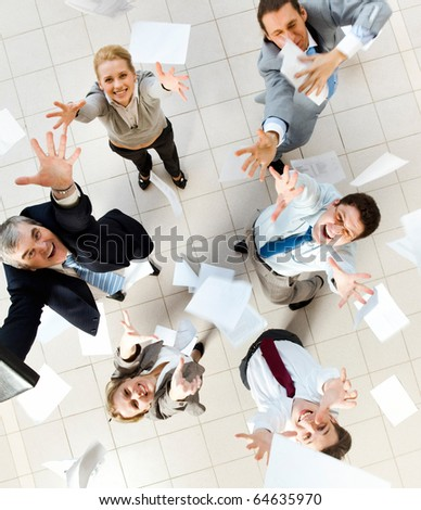 Above view of several successful partners throwing papers in joy - stock photo