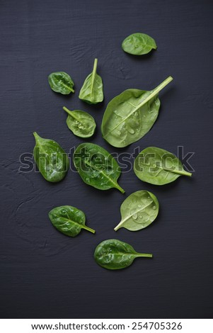 Above view of spinach leaves over black wooden surface - stock photo