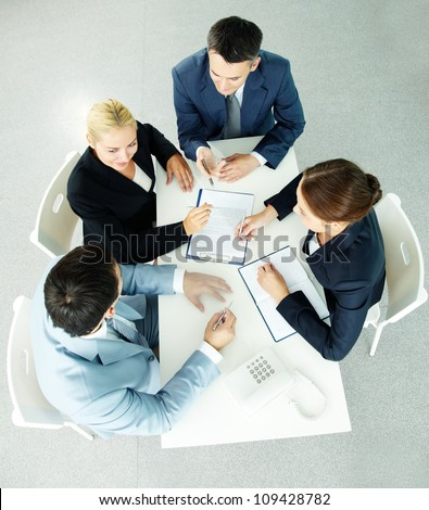 Above view of successful partners interacting at meeting - stock photo