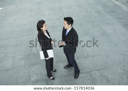 Above view of two Happy Chinese Business colleagues standing outside office & talking to each other. - stock photo