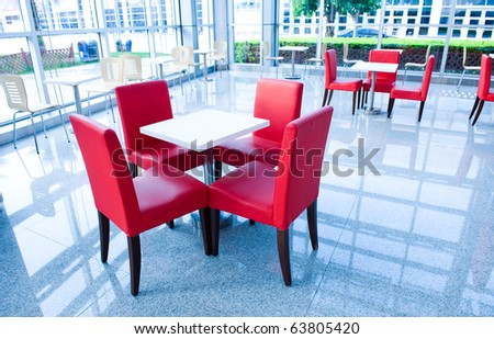 Above view of white table with four red chairs near by. - stock photo