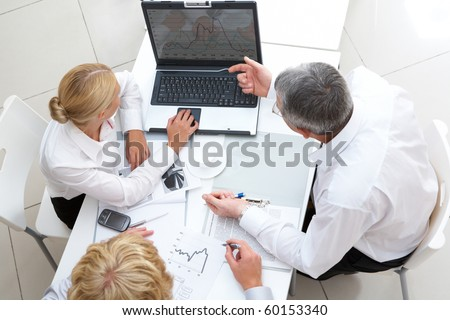 Above view of workteam discussing computer project at meeting - stock photo