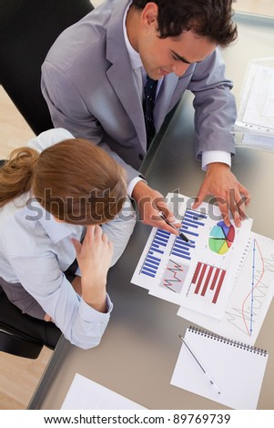 Above view of young business people working with statistics - stock photo