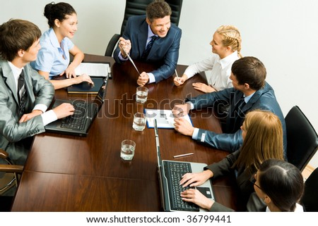 Above view of young co-workers working with papers and consulting each other - stock photo