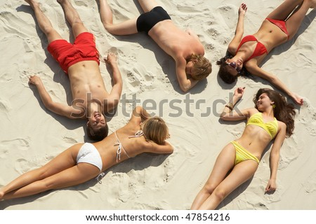 Above view of young slip teens sunbathing at beach - stock photo