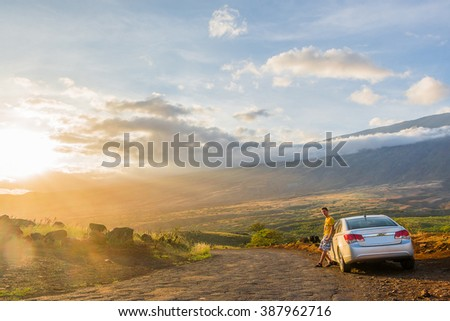 Absolutely amazing sunset view on the island of Maui, Hawaii with a volcano on the background and a young man standing next to a car and looking into the horizon - stock photo