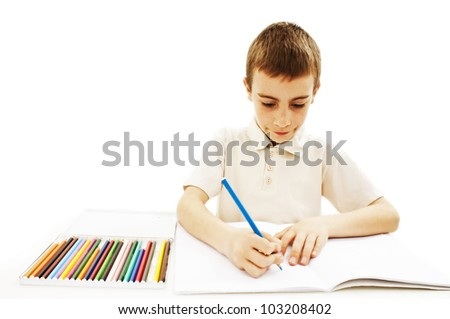 Absorbed little boy drawing with colorful pencils isolated on white background - stock photo