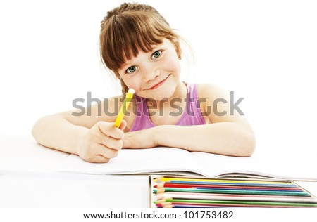 Absorbed little girl drawing with colorful pencils isolated on white background - stock photo