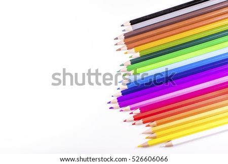 Abstract angle of jagged row of coloured pencils on white with space for text