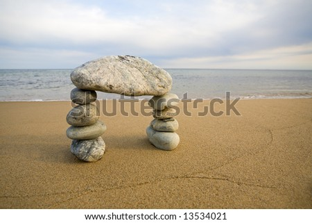 Abstract arch from a natural stones on a background of the sea - stock photo