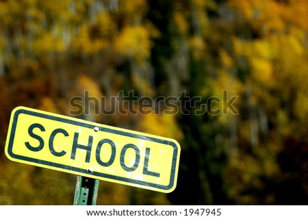 abstract autumn color with yellow school road sign tilted in left lower corner - stock photo