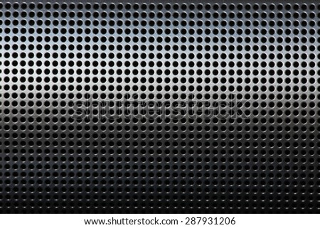 abstract background based on closeup of a high technology precision metal protective cover. Many small circular perforation holes. Object is lit from top for interesting lighting pattern. Horizontal.