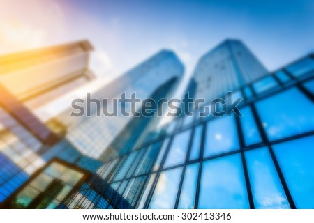 Abstract background blur bokeh image of modern skyscrapers in new business district in beautiful evening light at sunset with lens flare filter effect - stock photo