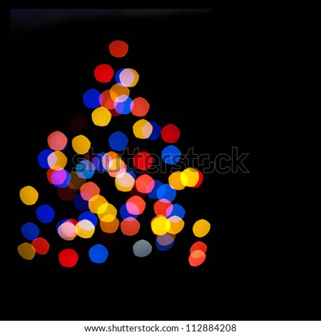 Abstract background - blurred colorful circles bokeh of Christmaslight in the form of a Christmas tree against dark background