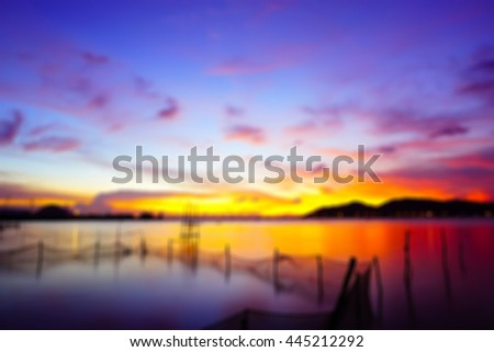 Abstract background blurry image of lake view on evening time after sunset with,silhouette island and fishing net in lake select focus with shallow depth of field:ideal use for background.