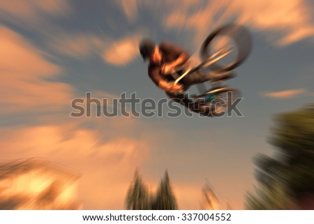 Abstract background . Boy on a BMX mountain bike jumping. Motion blur photo - stock photo