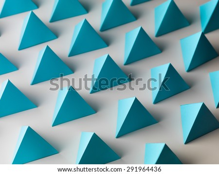 abstract background consisting of blue pyramid paper shapes - stock photo