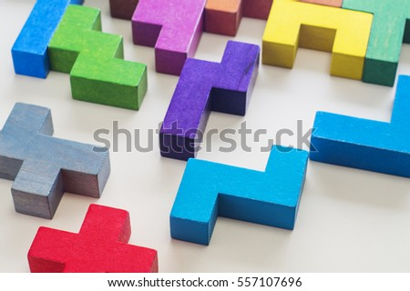 Abstract Background. Different colorful shapes wooden blocks on beige background background, close-up. Geometric shapes in different colors. Concept of creative, logical thinking or problem solving.
