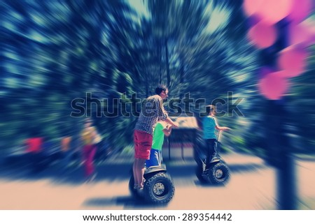 Abstract background. Father and children riding a Segway in the park.  Blur effect defocusing filter applied, with vintage instagram look. - stock photo