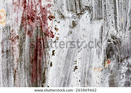 Abstract background gloomy concrete wall, casually painted dark paint, weathered with cracks and scratches in the wall hammered a rusty nail. Requires urgent repairs. Great background or texture. - stock photo