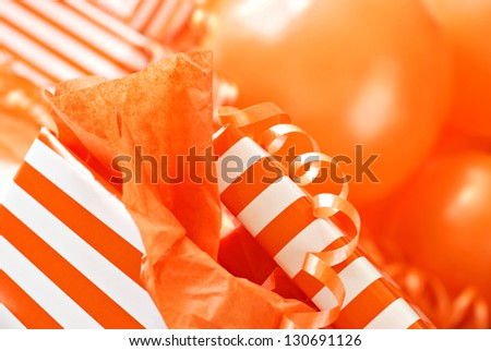 Abstract background image of orange and white gift box with ribbons and balloons.  Macro with extremely shallow dof.  Selective focus on corner of box lid. - stock photo