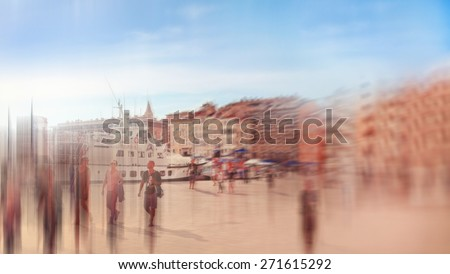 Abstract background. Marseilles, Old port (Vieux-Port) with people walking along the promenade.  Radial zoom blur effect defocusing filter applied, with vintage instagram look. - stock photo