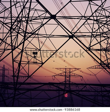 Abstract background of electricity pylons over purple sunset, conceptual image of invironmental damage and pollution of nature
