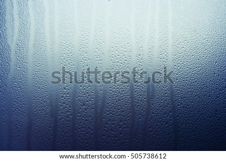 Abstract background of soft raining waterdrops flowing down the mirror.