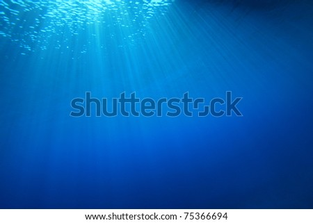 Abstract background of sun rays in clear blue water - stock photo