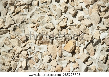 Abstract background paving consisting of small pebbles embedded in cement creme color